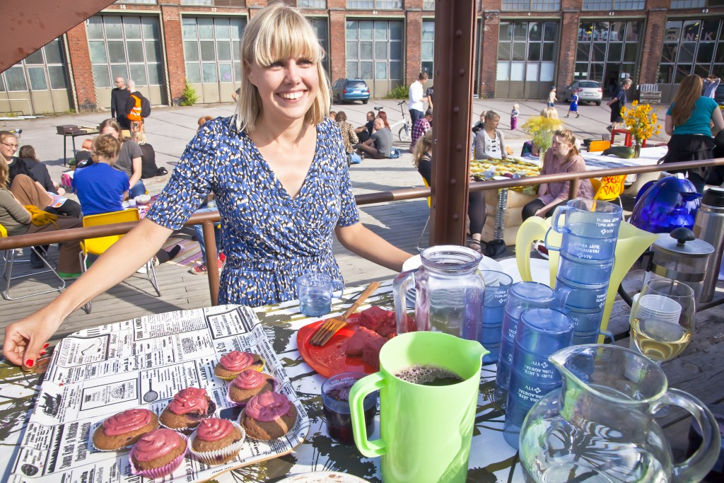 Iiris Virtasalo serves organic black currant cup cakes and blueberry juice on the international Restarant Day 21st of August 2011 at the old train depot area in Helsinki, Finland.